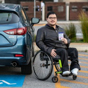 Young man in a wheelchair next to his car, holding up an ACROD permit.