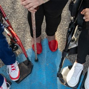The feet of 3 different ACROD permit holders standing over an ACROD Parking Bay.