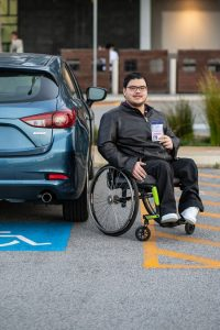 Young man in wheelchair holding up his ACROD parking permit