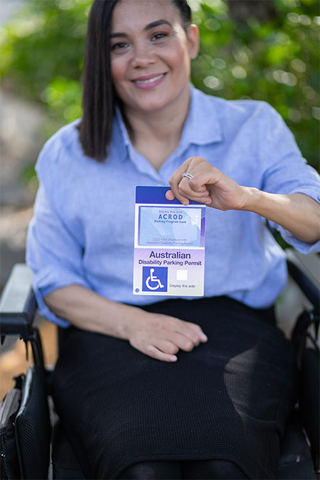 Young woman in a wheelchair holding up An ACROD Disability Parking Permit